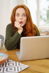 überraschte frau mit laptop zu hause