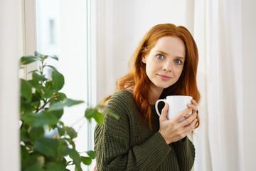 frau steht in ihrer wohnung am fenster und trinkt eine tasse tee