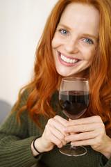 lachende frau hält ein glas rotwein in der hand