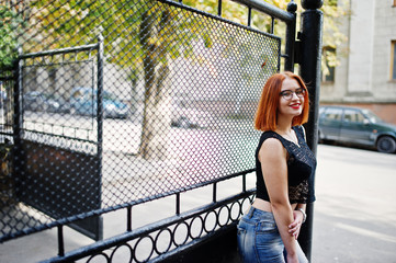 Red haired girl in glasses with red handbag posed at street of city.