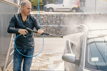 Man washing his car with using a high pressure water jet