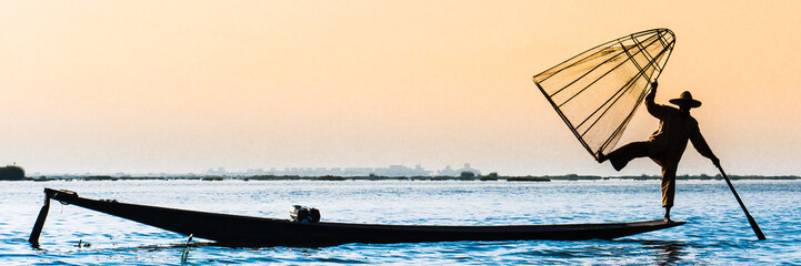 The silhouette of the fisherman using the traditional fishing device with a wooden boat at Inle lake, Myanmar
