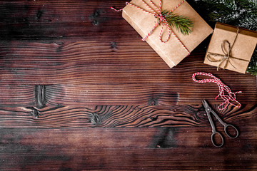 packaging christmas gifts in boxes on wooden background top view