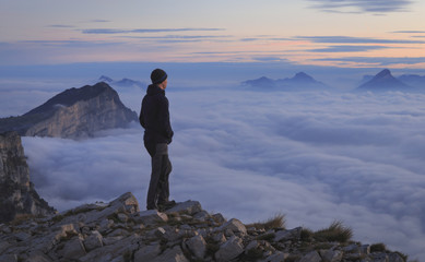 Fotomurales - A hiker looking over a sea of clouds in the mountains at dawn.