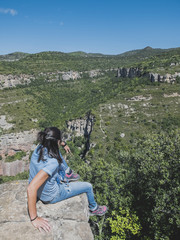 Young woman sitting on edge above the valley