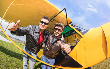 Happy best friends taking selfie at aeroclub with ultra light airplane - Luxury friendship concept about young people with thumbs up having fun together outdoors - Sunny afternoon vivid color tones