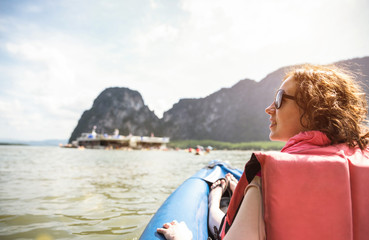 Young woman traveler with life jacket at sunset ride on kayak island hopping - Wanderlust travel concept with adventure girl tourist wanderer on excursion in Thailand - Warm vintage sunshine filter