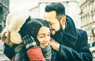 Young hipster couple of lovers at beginning of love story - Handsome man whispers sexy kisses in beautiful woman ear - Winter love concept with boyfriend and girlfriend - Soft focus on girl face