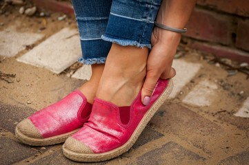 Young female touching her rubbed foot. New shoes cause sore skin on foot, rubbing foot blister problem, callus stock image.