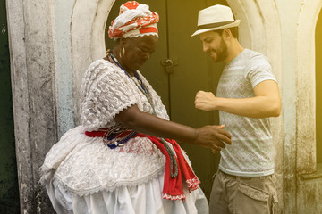 Tourist dancing with 'Baiana' woman in Pelourinho, Salvador, Bahia, Brazil