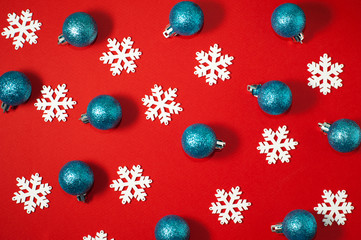 White snowflakes and blue glitter new year balls on a red background. Christmas ornament pattern photo