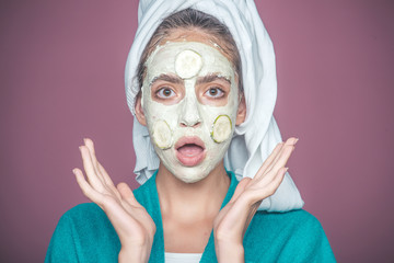 Girl with cucumber mask on surprised face on violet background