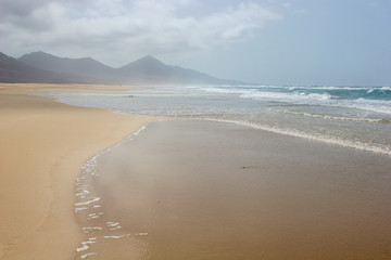 Ocean surf on magnificent Cofete beach in secluded part of Fuerteventura, Canary Islands, Spain