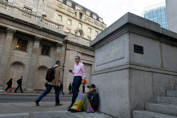 A homeless man waits for donations in front of the Bank of England as workers make their way into work in the City of London