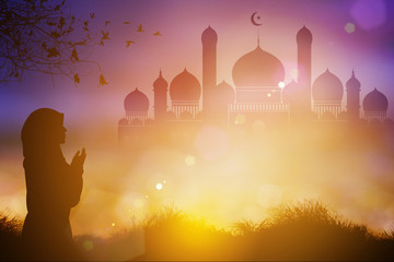 silhouettes of a woman praying during  blurred nature sunset with Muslim mosque  background ,Concept of Islam is the religion
