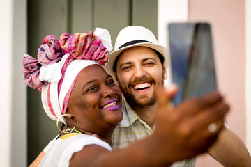 Tourist taking selfie photos with 'Baianas' women in Pelourinho, Salvador, Bahia, Brazil