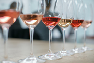 Row of glasses with white and rose wines prepared for tasting