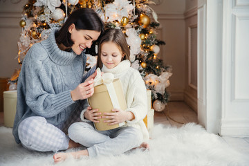 Indoor shot of adorable girl and her mother sit crossed legs, open wrapped present box, have intrigue what is there, sit against adorned New Year or Christmas tree, have sincere gentle smiles on faces