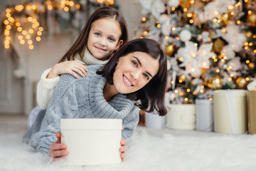 Children, family and celebration concept. Adorable female in knitted sweater holds white present box and small kid stands behind her back, have good mood before New Year`s Eve. Waiting miracle
