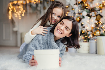Happy female model with short dark hair and her adorabe small girl have fun together, celebrate Christmas, exchange presents, have smiling expressions, have joy. Friendly family with presents