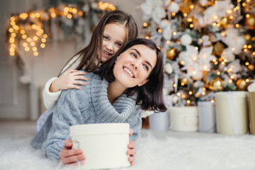 Portrait of happy mother and daughter spend free time together, embrace each other, have pleasant smiles, hold wrapped present boxes, celebrate New Year or Christmas together. Holidays concept