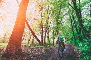 A man on a bicycle in the woods