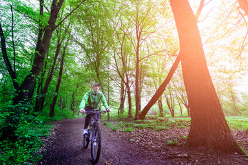 A man rides a bicycle through the woods