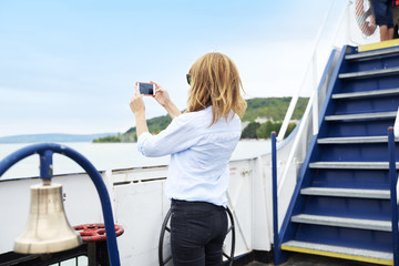 Memorable moments. Rear view shot a casual woman standing on the boat at taking picture with her cell phone.