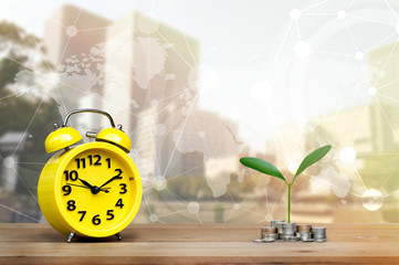 Yellow alarm clock and coins stack with tree top on wood table surface background textured with blurred building ,world map, selective focus, with copy space for product or business financial concept.