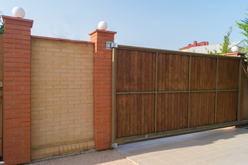 Brown automatic wooden gates of private house. Inside view