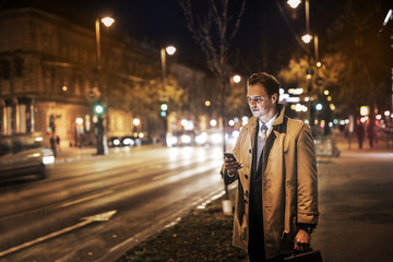 Businessman standing in the street at night