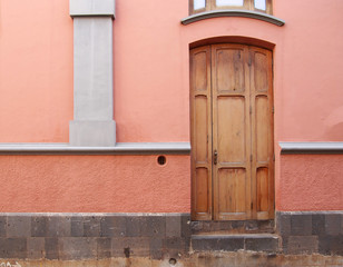 old wooden brown door in a pink painted spanish house with white plaster details
