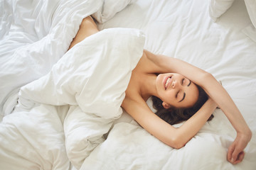 portrait of young woman lies in bed early in the morning. pretty smiling woman closing her eyes and wrapping herself in a blanket