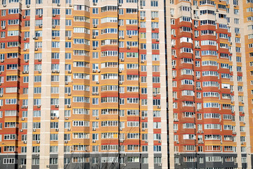 Facade of a large multi-storey block of flats with many apartments front view closeup