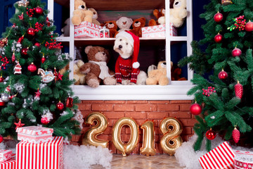 Decorated west highland white terrier dog as symbol of 2018 New Year in red sweater sitting on shelf with teddy bears in winter holidays and christmas tree on background