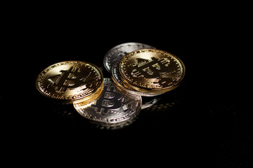 Stack ofgold and silver bitcoins on black background