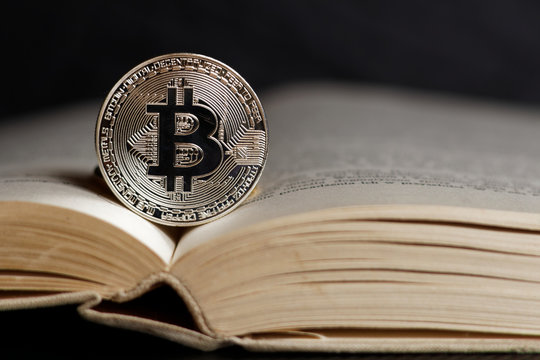 SIlver bitcoin on open book page