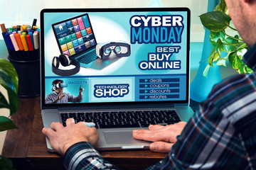 man with laptop in site web with an announcement of discounts in shop online for Cyber Monday / man in laptop at home searching deals in website internet store to purchase electronics devices online