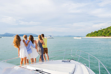 Group of young people looking outside from modern yacht. Back view. Luxury vacation concept.