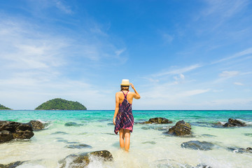 Girl in dress and hat walking into sea with blue clear water. Sky and island on background. Back view.