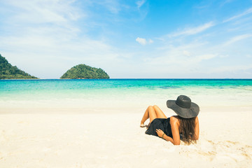 Vacation concept: woman in black hat on beautiful beach looking on island in blue water.