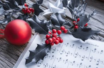 Alte handgeschriebene Musiknoten mit Ilex Zweig, roten Beeren, Weihnachtsstern und roter Weihnachtskugel, Weihnachten, xmas