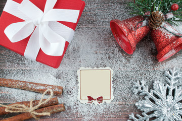 Red box - Christmas gift and blank gift tag on the wooden snowy background