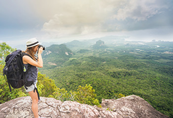 Traveller- photographer with backpack  taking photo from mountain peak in cloudy day. Travel concept.