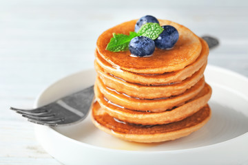 Plate with tasty buckwheat pancakes on table, closeup