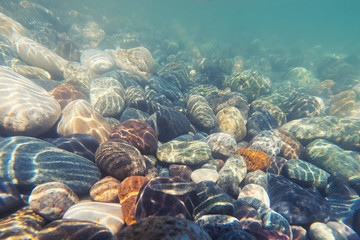 Underwater shot: pebble on seabed. Selective focus.
