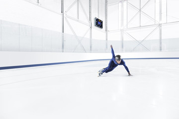 Young man practicing speed skating at ice rink