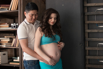 A pregnant young woman and a man are standing side by side, the man put his hand on his stomach. Happiness. Expectation. The blue skirt.
