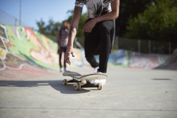 Teenage boy with skateboard in skatepark