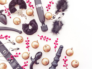 Christmas or New Year background with a variety of sex toys, golden balls and red berries